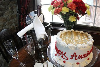 White cake in the foreground with wine glasses and flowers in front of a window and a stone wall in the background.
